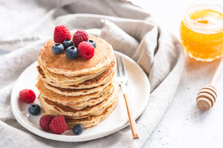 Pancakes with berries and honey on white plate, selective focus