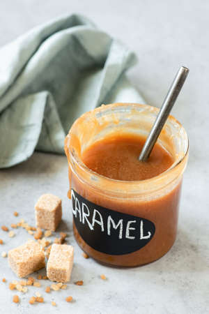 Homemade caramel sauce in jar on grey concrete background, vertical composition, selective focus Stock Photo