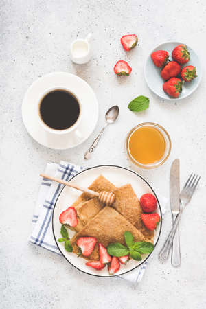Crepes or blini with honey, strawberries and cup of coffee on white concrete background. Top view of tasty healthy breakfast