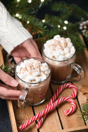 Hot Chocolate With Marshmallows And Candy Cane. Woman hands holding mug of hot chocolate or hot cocoa drink. Winter, Christmas or New Year comfort food concept