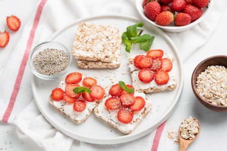 Rice crispbread with strawberries and curd cheese ricotta on white plate. Healthy snack, vegetarian food, healthy sweet appetizer or breakfast concept