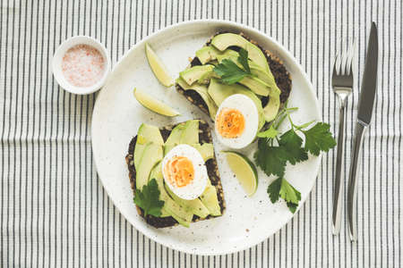 Avocado and egg on rye bread on a plate on textile, top view. Healthy breakfast, healthy eating or vegetarian diet concept