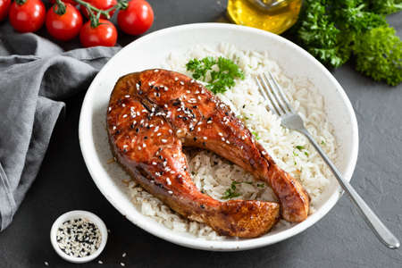Teriyaki salmon steak with rice on white plate. Healthy food Stock Photo
