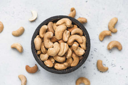 Cashews in bowl on concrete background, top view selective focus