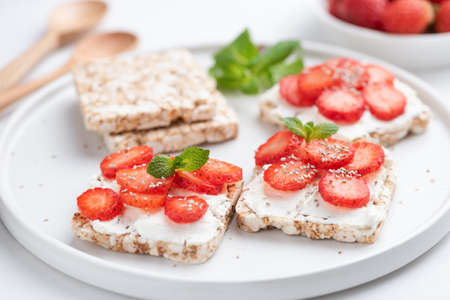 Healthy rice crispbread snack with curd cheese and strawberries on white plate. Healthy sweet snack, vegetarian snack