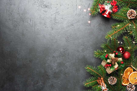 Christmas Background. Fir Tree Decorations Gift Box On Black Concrete With Copy Space. Christmas or New Year festive card Stock Photo