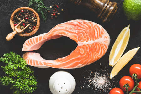 Salmon steak, spices and vegetables for cooking on black background, table top view, toned image