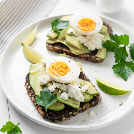 Toast with avocado, feta cheese and boiled egg on white plate, closeup view. Square crop. Avocado egg sandwich Stock Photo