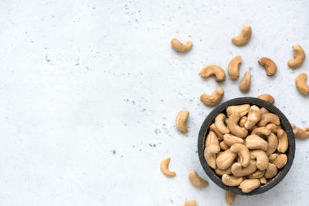 Cashew nuts in bowl on grey concrete background with copy space for text. Top view, healthy vegetarian food