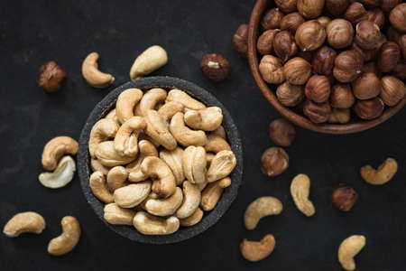 Mixed nuts on black concrete background, top view. Cashews and hazelnuts in bowl