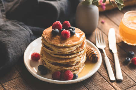 Pancakes with berries and honey. Tasty breakfast with pancakes, blueberry, raspberry and honey on rustic wooden table background. Toned image, soft morning light