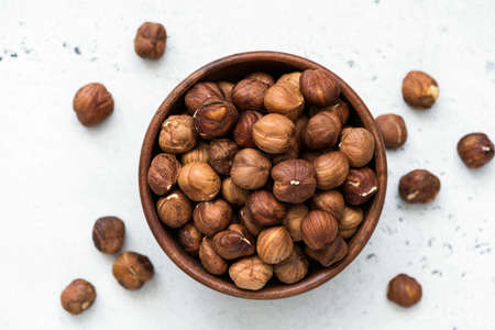 Hazelnuts in bowl. Unpeeled hazelnuts in wooden bowl on white background