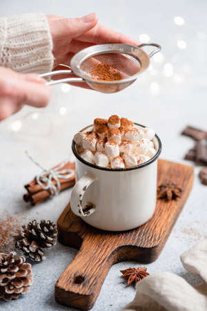 Hot chocolate with marshmallows in mug. Sifting cocoa powder over hot chocolate drink with marshmallows