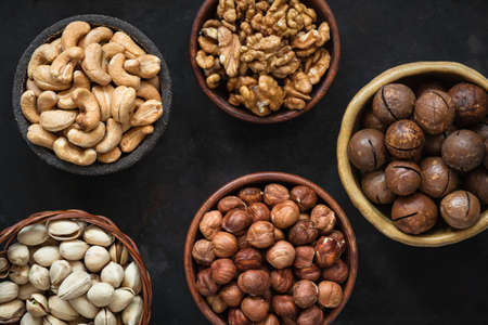 Various nuts in bowls on black background. Hazelnut, cashew nuts, pistachios, macadamia and walnuts. Top view Stock Photo