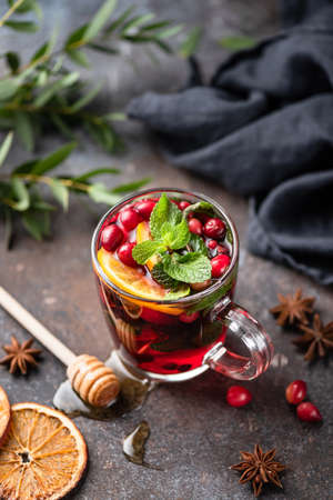 Hot spicy cranberry mulled wine or cranberry tea in glass cup decorated with orange peel and mint leaf Stock Photo