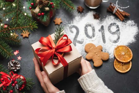 2019 Christmas New Year Greeting Card Gift Box. Hands Holding Gift Box. 2019 Number Written On Flour Stock Photo