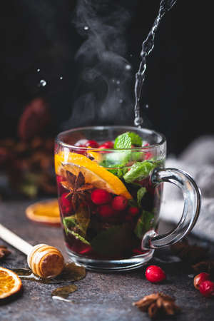 Hot fruit tea with spices, orange peel and mint. Steaming glass cup of hot tea, mulled wine with cranberries or spicy cranberry grog