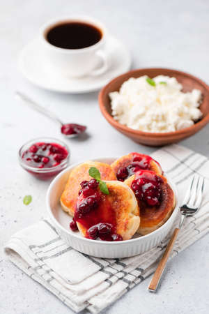 Cottage cheese fritters or syrniki with cranberry sauce on white plate served with black coffee. Selective focus Stock Photo