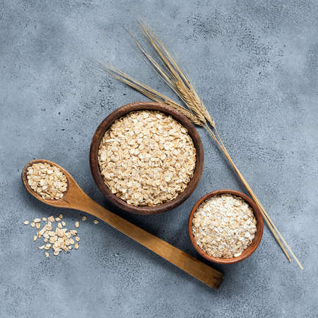 Rolled oats or oat flakes in wooden bowl on concrete