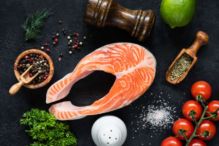 Raw salmon steak, vegetables and spices for cooking on black slate.