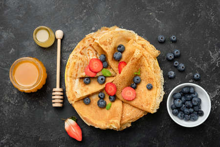 Crepes or blini with berries and honey on black concrete background, table top view