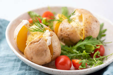 Baked potatoes with sour cream and cheese served with arugula tomato salad. Closeup view Фото со стока