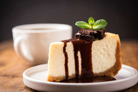 Cheesecake with chocolate sauce and cup of coffee. Slice of classical New York cheesecake poured with chocolate sauce and decorated with mint leaf Фото со стока