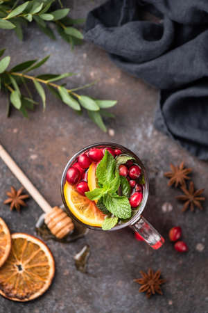 Tea with cranberry, orange, spices and mint in glass cup. Top view. Comfort winter or autumn drink