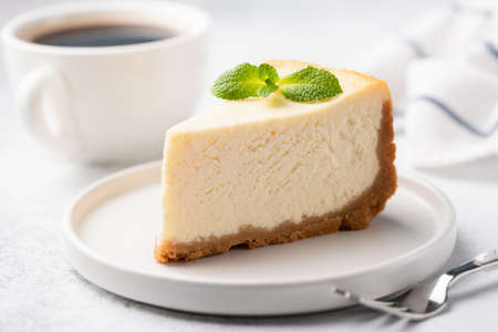 Tasty Plain New York Cheesecake On White Plate Decorated With Mint Leaf. Closeup View