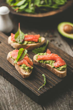 Healthy Open Sandwiches With Avocado and Salmon On Wooden Cutting Board. Selective focus, Toned image Фото со стока