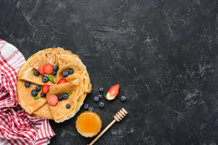Tasty homemade crepes with honey and berries on black concrete background. Table top view. Maslenitsa food