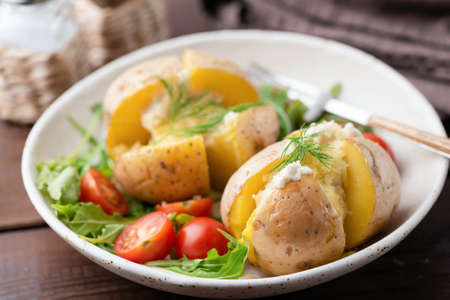Baked stuffed potatoes with cheese, sour cream and dill on a plate. Healthy tasty dinner