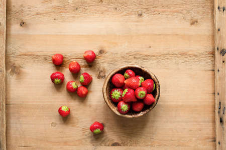 Fresh strawberries on wooden background, top view. Copy space for text. Harvest of fresh organic strawberries
