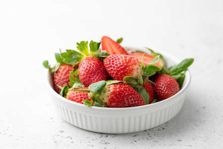 Fresh strawberries in bowl on white background, horizontal view, selective focus. Tasty strawberries. Healthy food