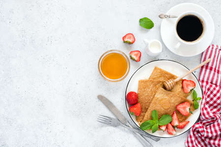 Crepes, thin pancakes or blini with strawberries, honey, coffee on concrete background. Top view, copy space for text