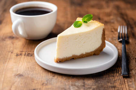 Cheesecake and cup of coffee on wooden table. Coffee and cake. Horizontal view Фото со стока