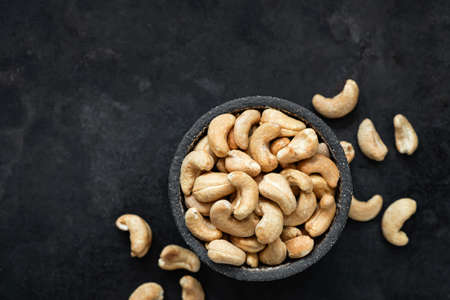 Cashew nuts in bowl on black background. Top view, copy space for text. Healthy snack, vegetarian food, beer snack Фото со стока