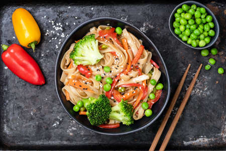 Vegetable stir fry with udon noodles, broccoli, carrot, pepper and green peas in bowl on black background. Top view