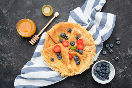 French Crepes or Russian Blini with berries, honey. Table top view, black concrete background