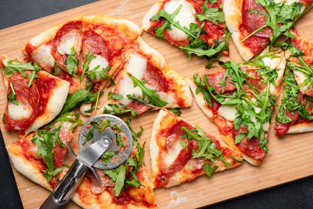 Pizza with salami, mozzarella and tomato sauce garnished with arugula. Sliced pizza. Table top view