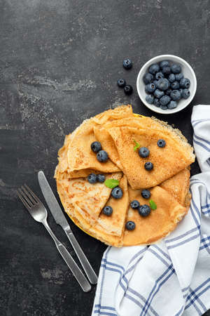 Blini, blintzes or crepes on black background served with fresh blueberries. Table top view, copy space for text, recipe, menu
