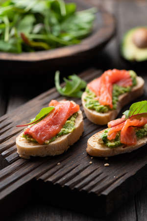 Mini toast bruschetta with salmon and avocado on wooden serving board. Selective focus