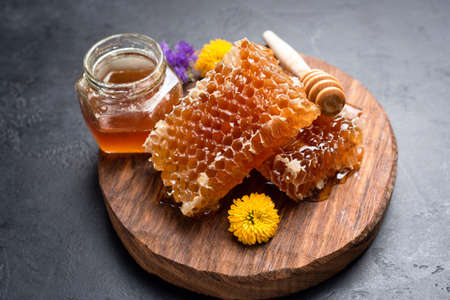 Honeycombs, flowers and jar of honey. Fresh natural raw honey