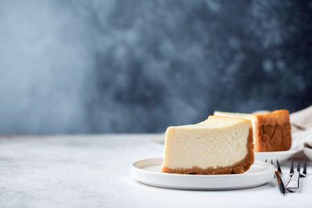 Klassischer einfacher New Yorker Käsekuchen über blauem konkretem Hintergrund. Platz für Text kopieren Standard-Bild