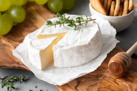 Tasty Brie Cheese or Camembert Cheese On Olive Wooden Serving Board. Closeup view