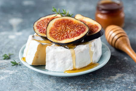 Brie or camembert cheese with fig and honey on plate. Tasty white cheese closeup view
