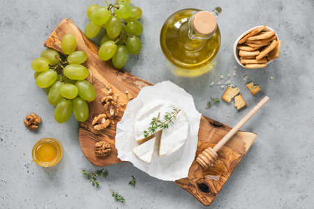 White cheese plate with crackers, honey, grapes. Assortment of wine snack, appetizer or gourmet dinner. Top view 스톡 콘텐츠