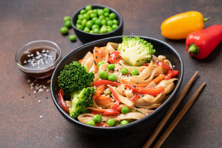 Asian udon noodle stir fry with broccoli, green pea, carrot and pepper in bowl. Tasty oriental asian food