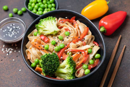 Asian noodle stir fry with vegetables in bowl. Udon noodles with broccoli, pepper, carrot and green peas