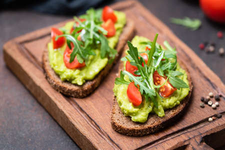 Healthy vegan toast with avocado, tomato, arugula on wooden serving board, closeup view, horizontal image. Snack, lunch or vegan breakfast 스톡 콘텐츠